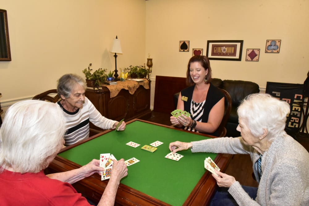 Residents and a staff member playing poker at Garden Place Columbia in Columbia, Illinois.