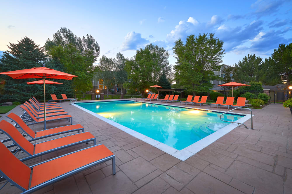 Beautiful resort-style swimming pool with a lush backdrop at Legend Oaks Apartments in Aurora, Colorado