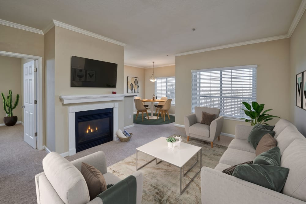 Living room and dining room with white accents and a fireplace at Skyecrest Apartments in Lakewood, Colorado