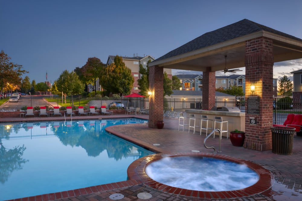 Swimming pool with a sundeck and lounge chairs at Promenade at Hunter's Glen Apartments in Thornton, Colorado