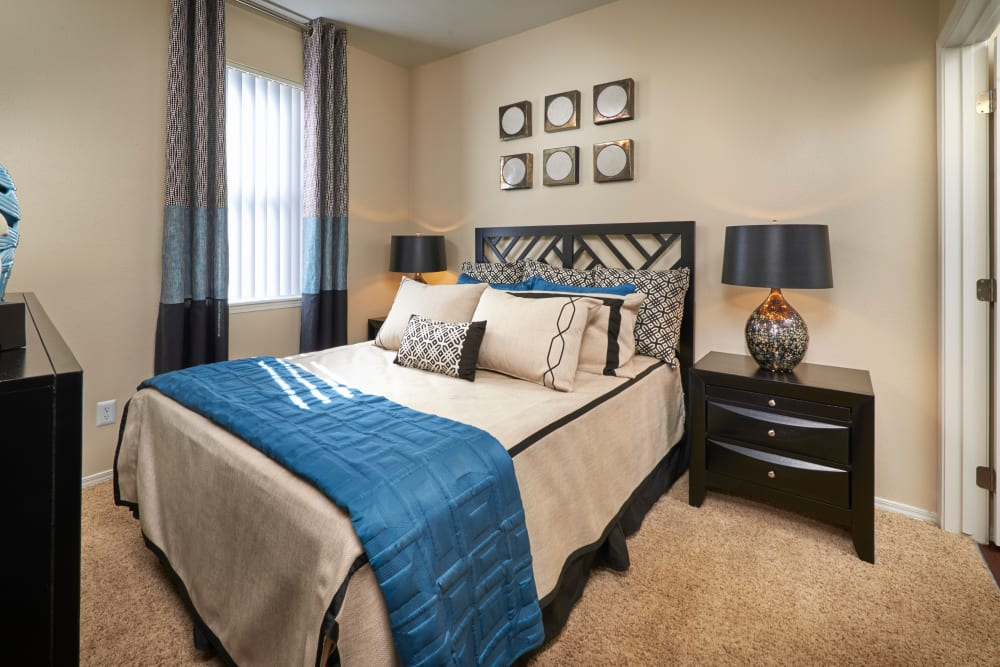 Master bedroom with a window for natural lighting at Promenade at Hunter's Glen Apartments in Thornton, Colorado
