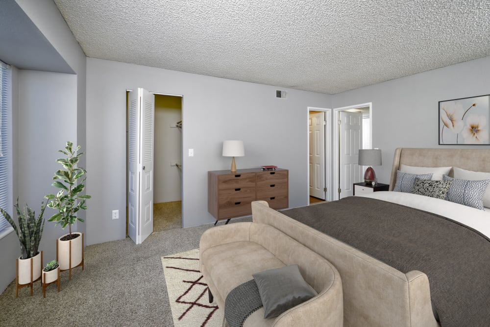 Decorated master bedroom with a large closet at Alton Green Apartments in Denver, Colorado