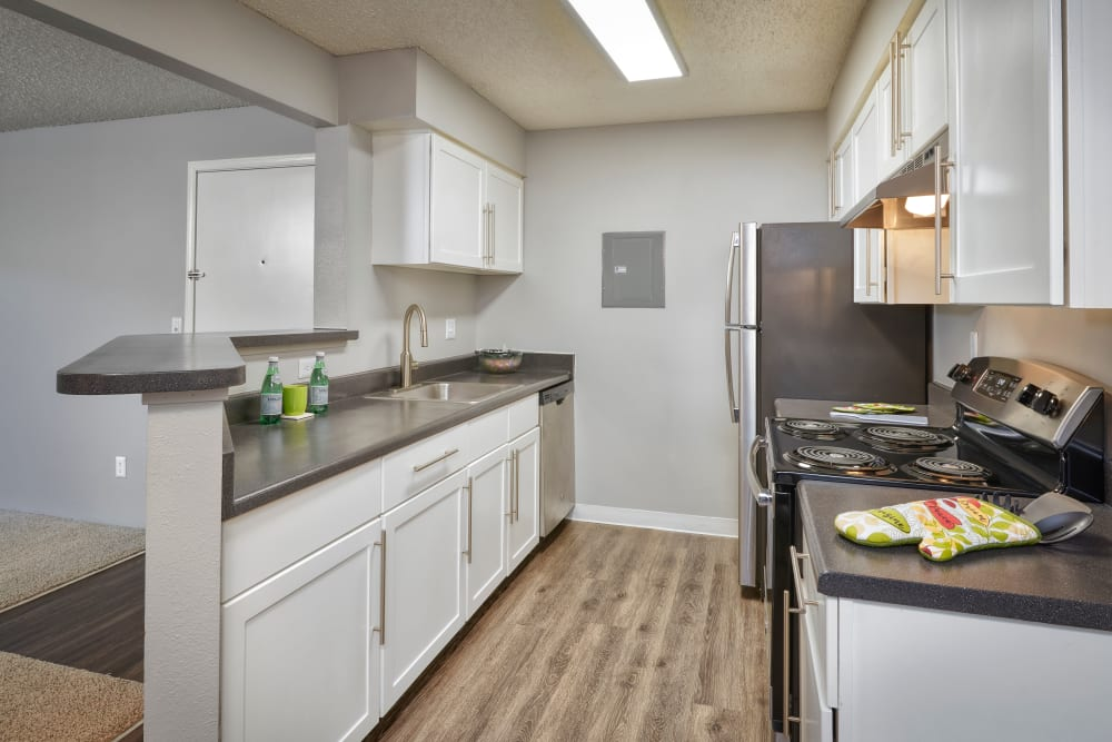 A kitchen with plenty of cabinet space at Alton Green Apartments in Denver, Colorado