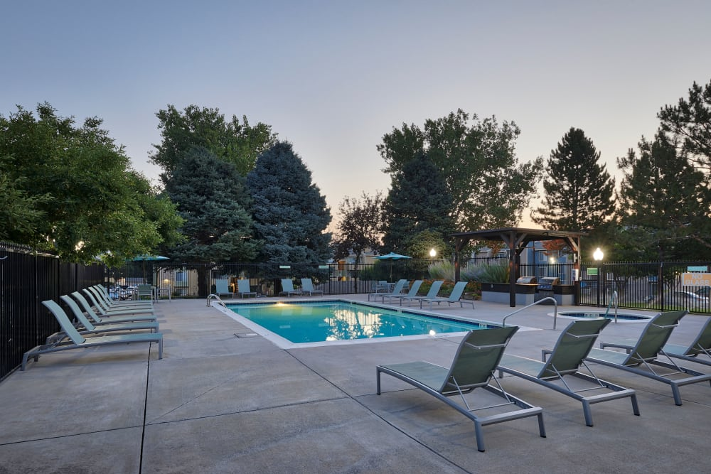 Beautiful resort-style swimming pool with lounge chairs and a barbecue area at Alton Green Apartments in Denver, Colorado