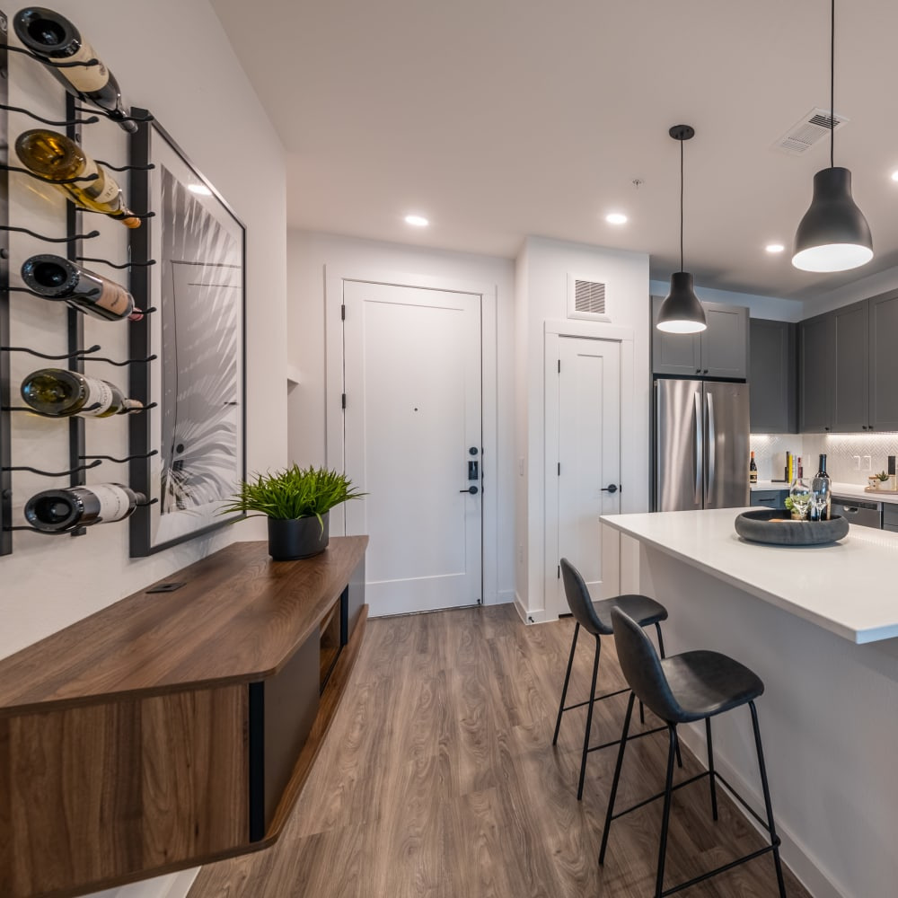 Kitchen breakfast bar area with cabinets and wine rack at The Langford in Dallas, Texas