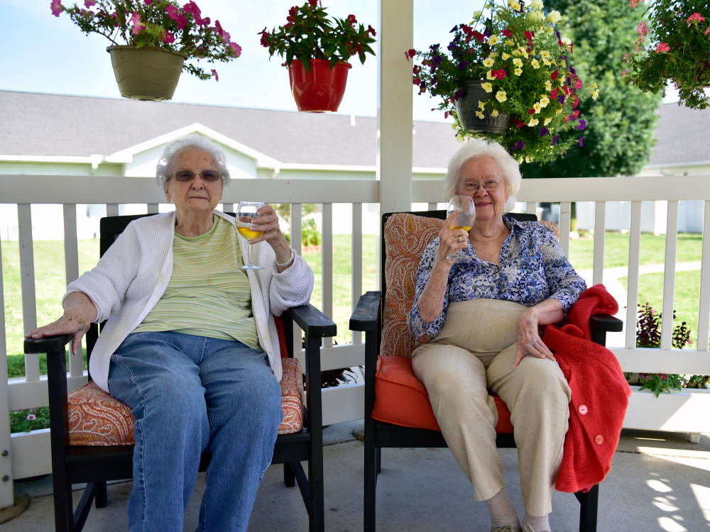 A handful of residents sitting in the outdoor walkway at Garden Place Columbia in Columbia, Illinois.