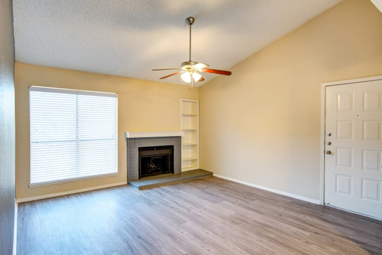 Beautiful hardwood floors and a ceiling fan in an apartment home's open-concept living area at Grayson Ridge in North Richland Hills, Texas