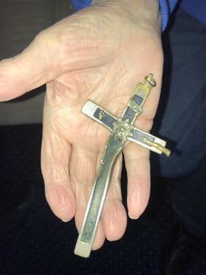 Hand holding a small cross