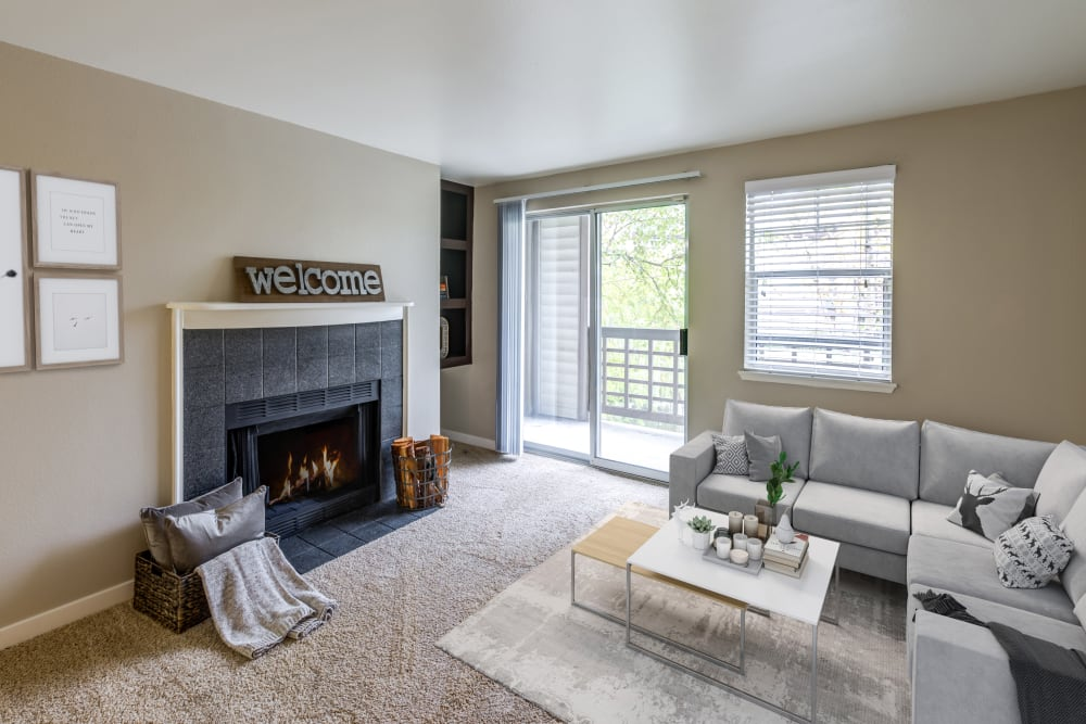 A living room complete with a fireplace at Olin Fields Apartments in Everett, Washington