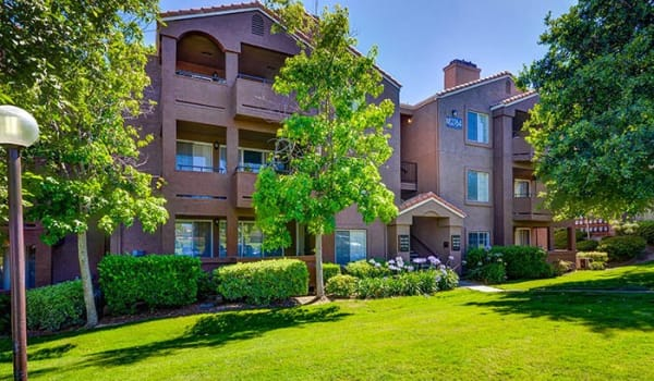 Exterior Building View with Open Grass Area and Lush Trees and Landscaping at Sierra Del Oro Apartments in Corona