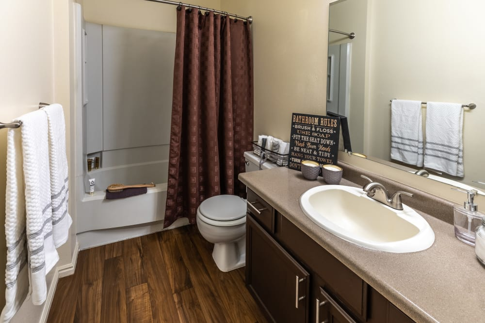 Bathroom with wood-style flooring at Shadowbrook Apartments in West Valley City, Utah