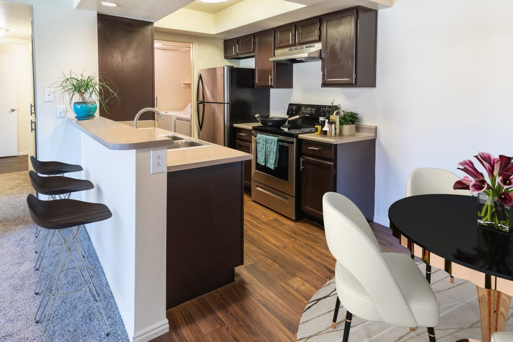 Kitchen with espresso cabinets and bar seating at Shadowbrook Apartments in West Valley City, Utah