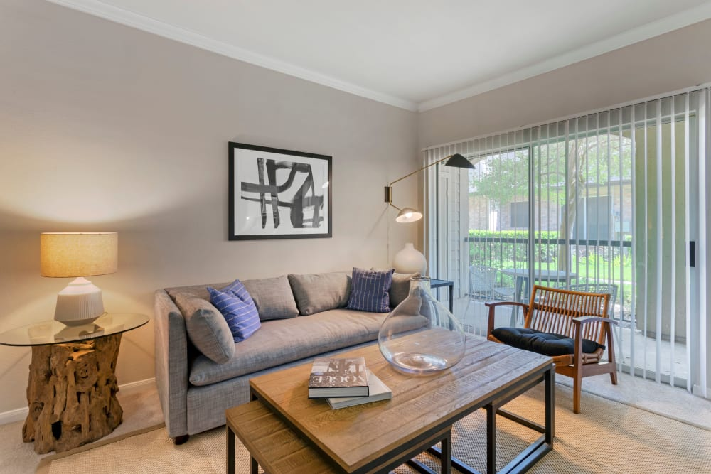 Model living room with large sliding doors opening onto a private patio and green space at Regency at First Colony in Sugar Land, Texas