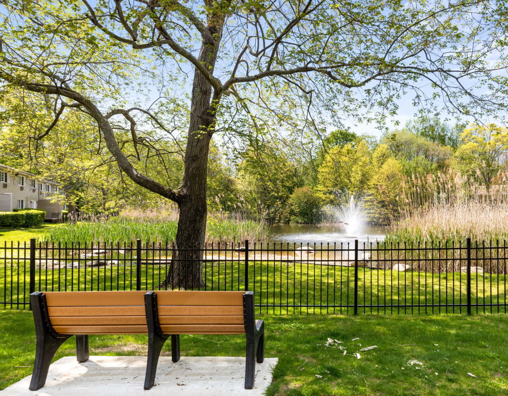 Park bench overlooking pond and water feature at Eagle Rock Apartments at Woodbury in Woodbury, New York
