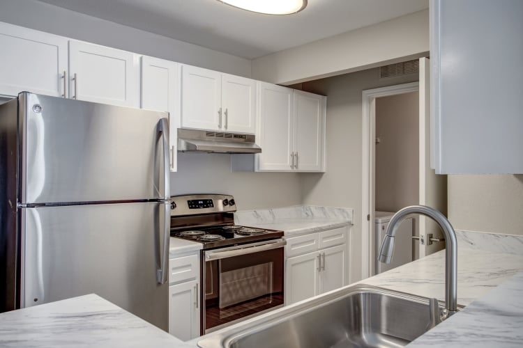 Modern kitchen with granite countertops in renovated apartment home at Kenwood Club at the Park in Katy, Texas