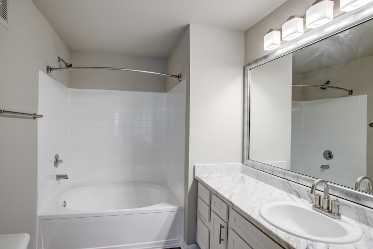 Large, well-lit bathroom with oversized vanity mirror in renovated home at Kenwood Club at the Park in Katy, Texas