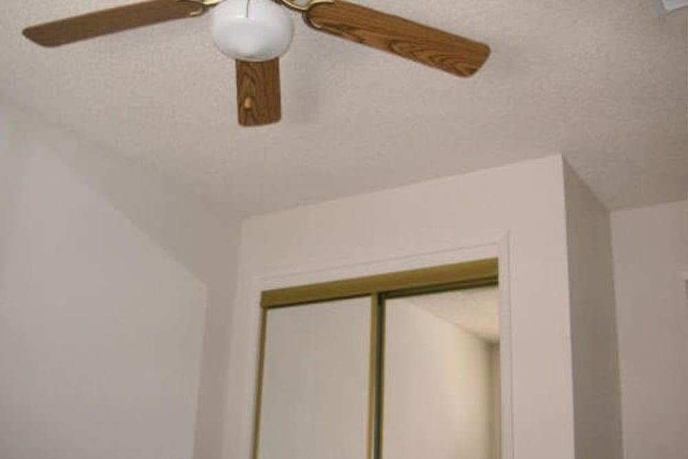 Bedroom with ceiling fan at Olympus Court Apartments in Bakersfield, California