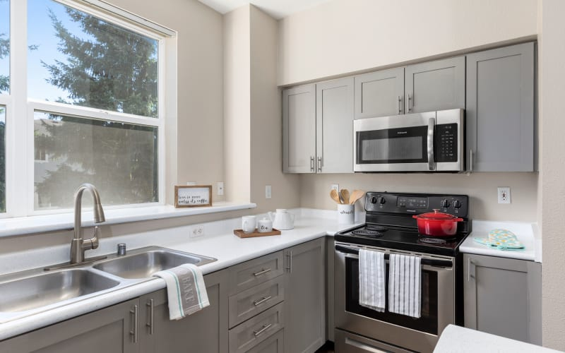 Renovated kitchen with trendy gray cabinets at HighGrove Apartments in Everett, Washington