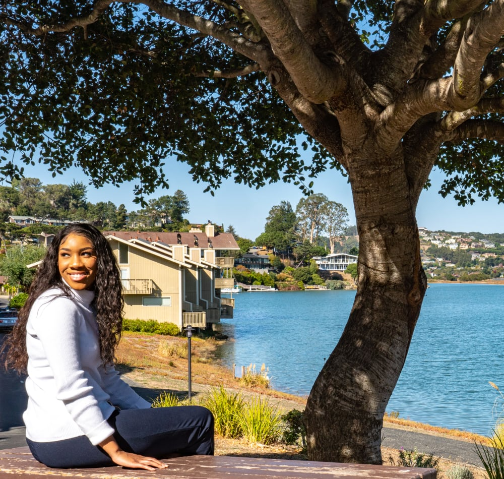 Resident sitting by a mature tree near the bay at Harbor Point Apartments in Mill Valley, California