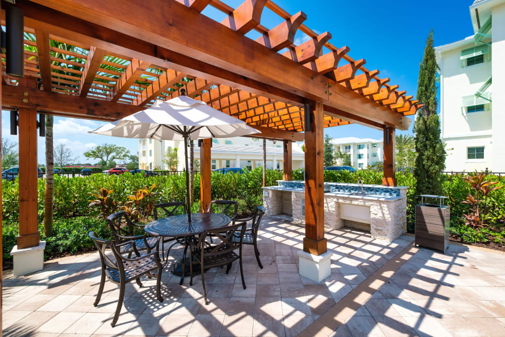 Outdoor grilling pavilion with a shaded table at Town Lantana in Lantana, Florida