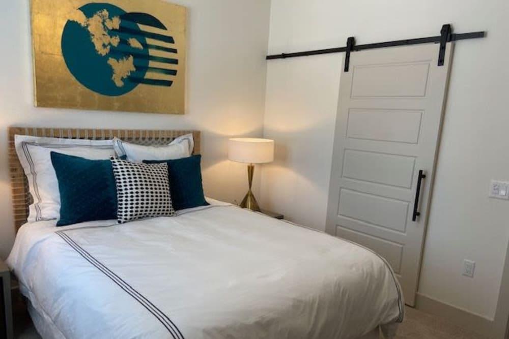 Comfortable Bedroom At The District at Chandler In Chandler, Arizona features barn door style sliding closet door