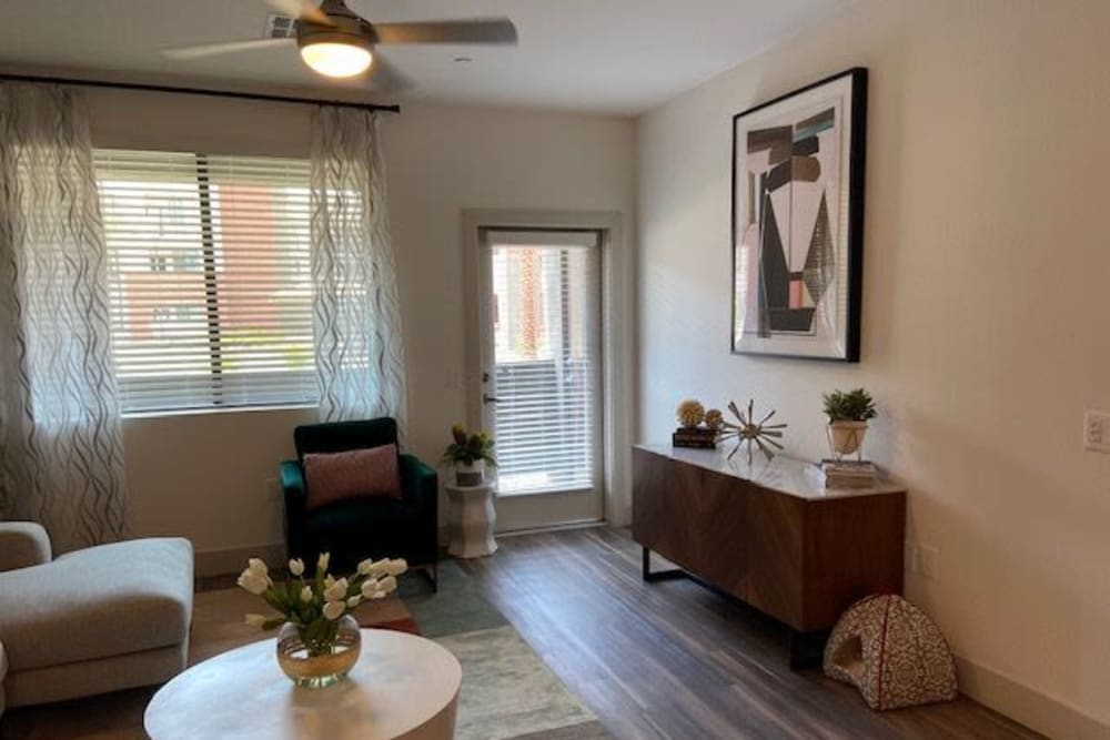 Stylish Living Room With Hardwood Floors And Comfortable Sitting Area At The District at Chandler In Chandler, Arizona