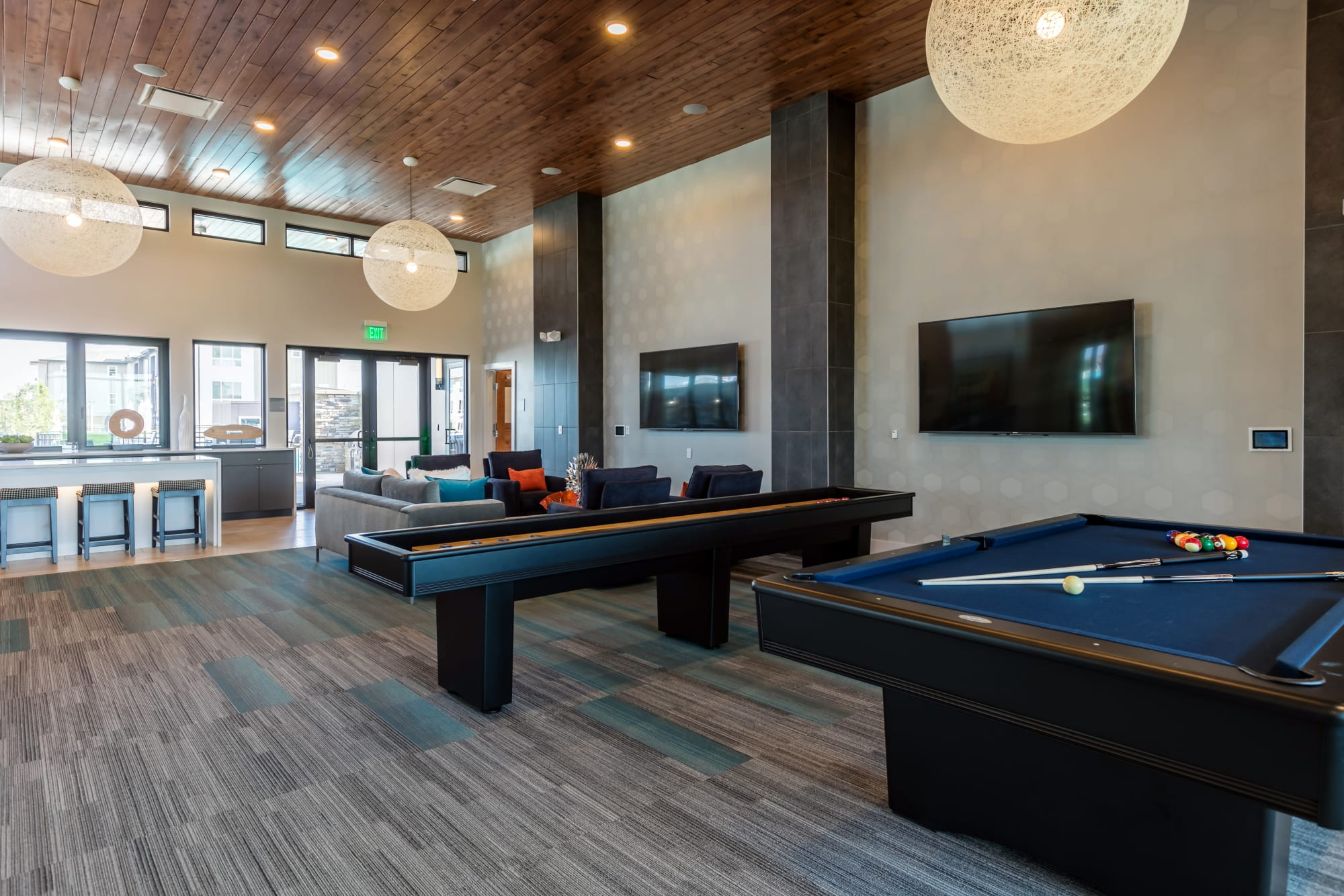 The game room, with billiards and shuffleboard, at Strata Apartments in Denver, Colorado
