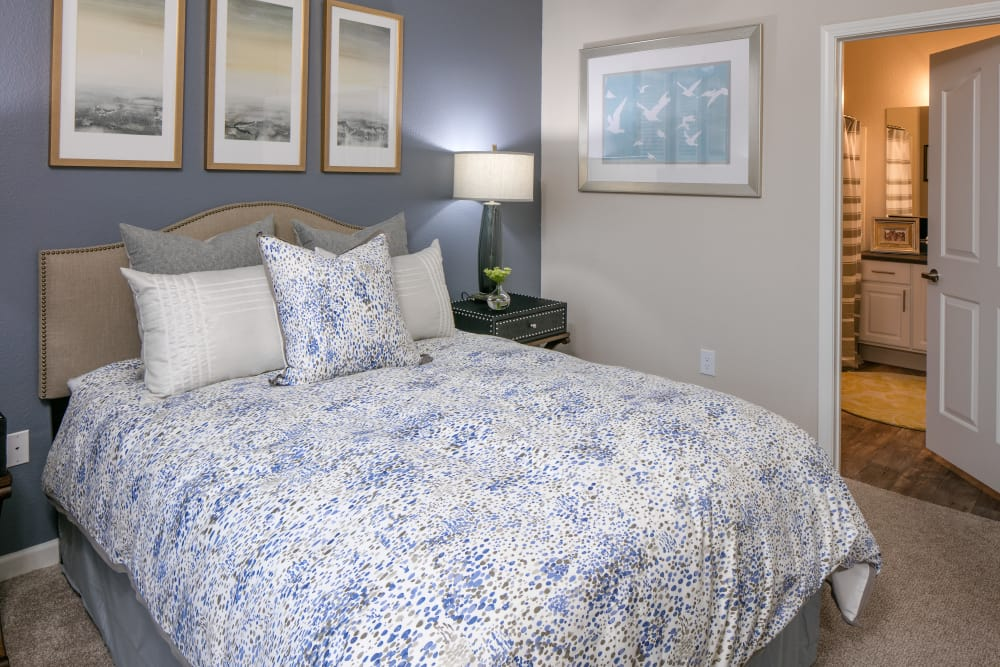 Model bedroom with lamp at Cortland Village Apartment Homes in Hillsboro, Oregon