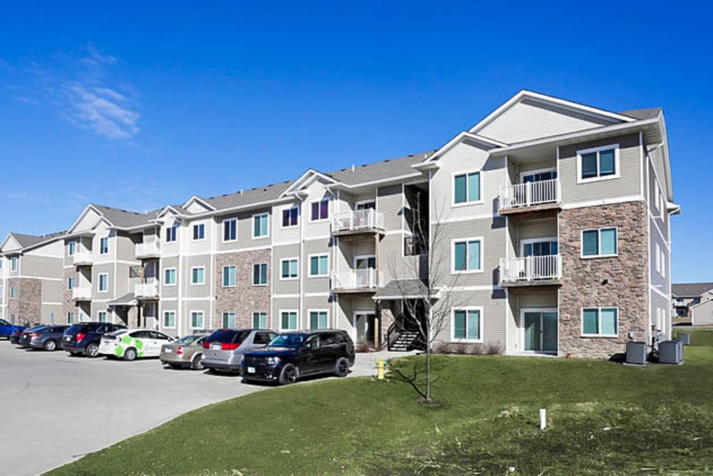 Exterior of apartments and parking lot at Johnston Heights in Johnston, Iowa