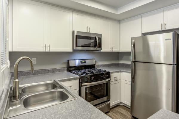 Modern white apartment kitchen with stainless steel appliances at Village Oaks in Chino Hills, CA