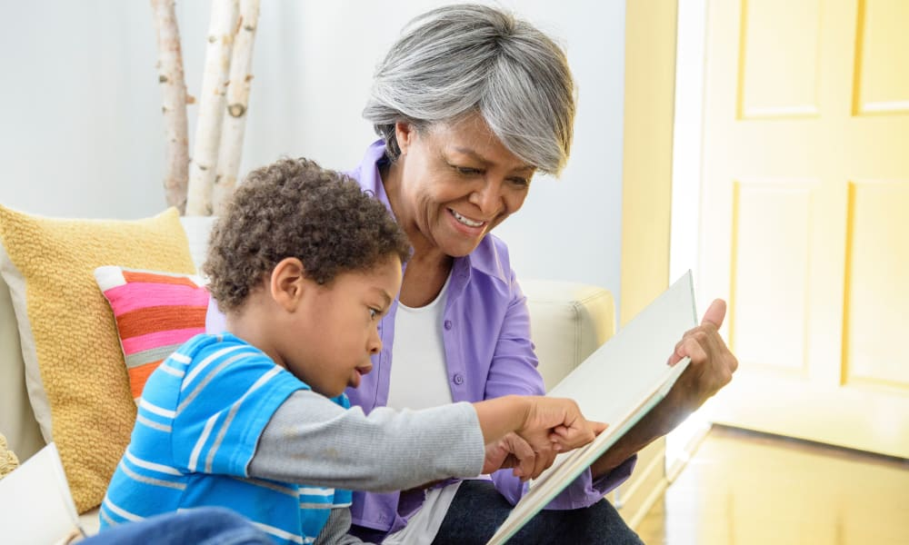 A resident and grandchild reading together at Amaran Senior Living in Albuquerque, New Mexico.