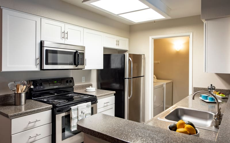 Renovated kitchen with stainless steel appliances at Sierra Del Oro Apartments in Corona, California