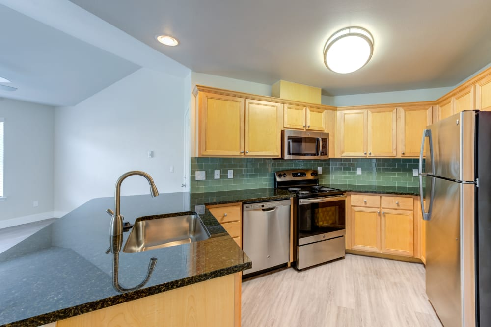Beautiful white cupboards and custom tile backsplash in model kitchen at Bradley Park Apartments in Puyallup