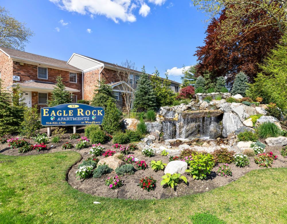 Beutifully landscaped entrance with water feature at Eagle Rock Apartments at Woodbury in Woodbury, New York