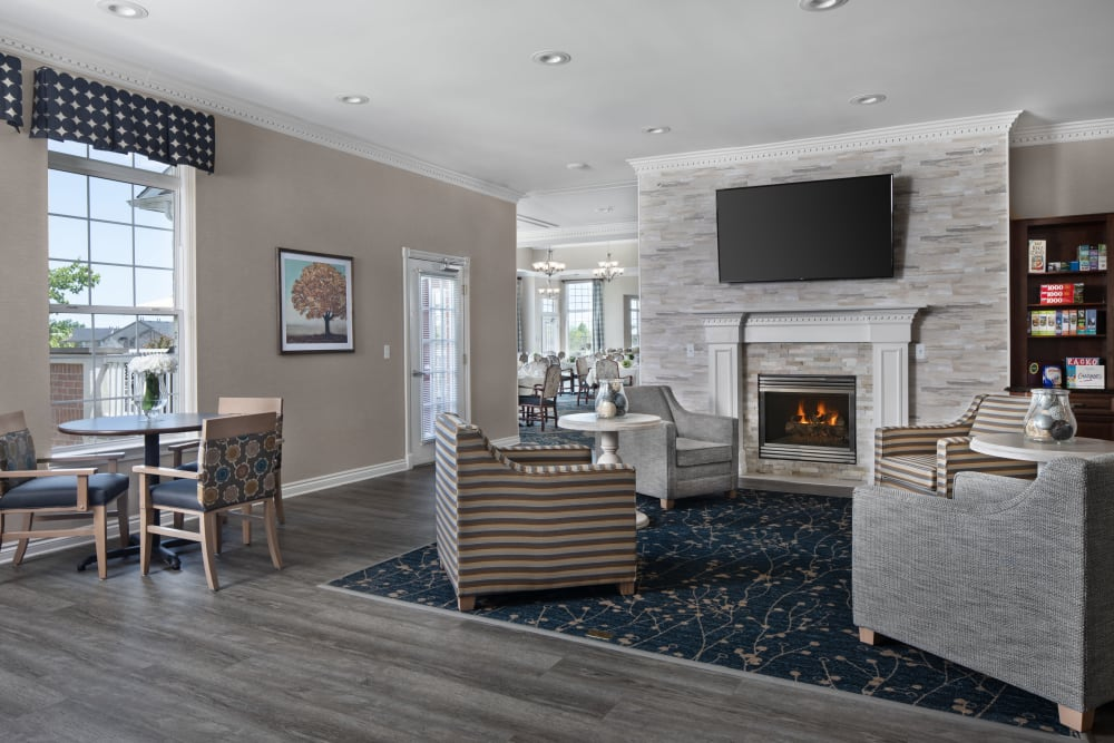 Lounge area with a fireplace at Waltonwood Lakeside in Sterling Heights, MI