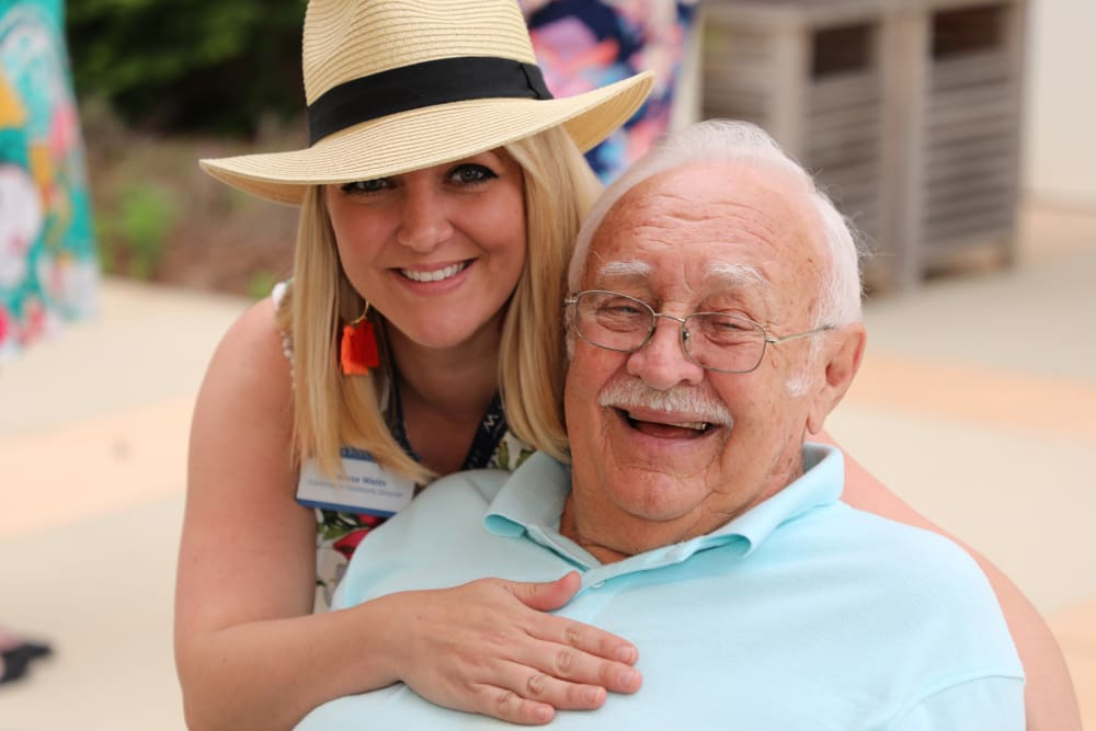 Team member and resident laughing at a BBQ at Merrill Gardens at Madison in Madison, Alabama.
