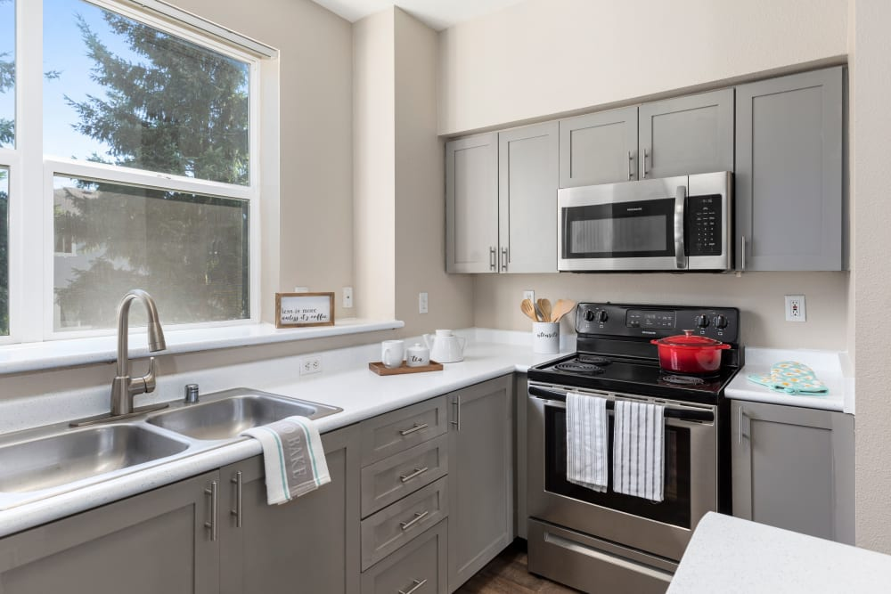 Kitchen with gray cabinetry at HighGrove Apartments in Everett, Washington