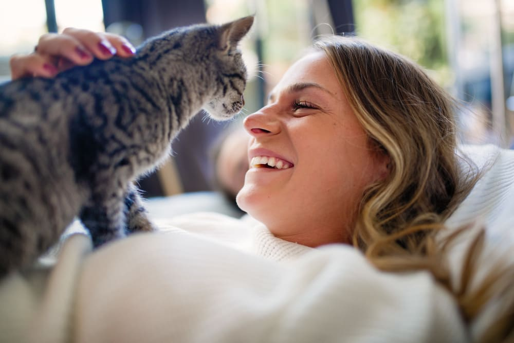 A women and her cat enjoying their new home at Promenade at Hunter's Glen Apartments in Thornton, Colorado
