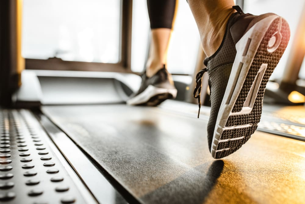 A woman jogging in the fitness center at Newport Crossing Apartments in Newcastle, Washington