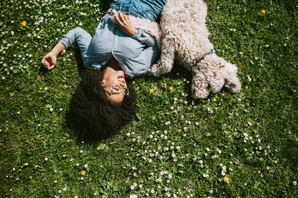 Woman lying in the grass with her dog at Telegraph Arts in Oakland, California