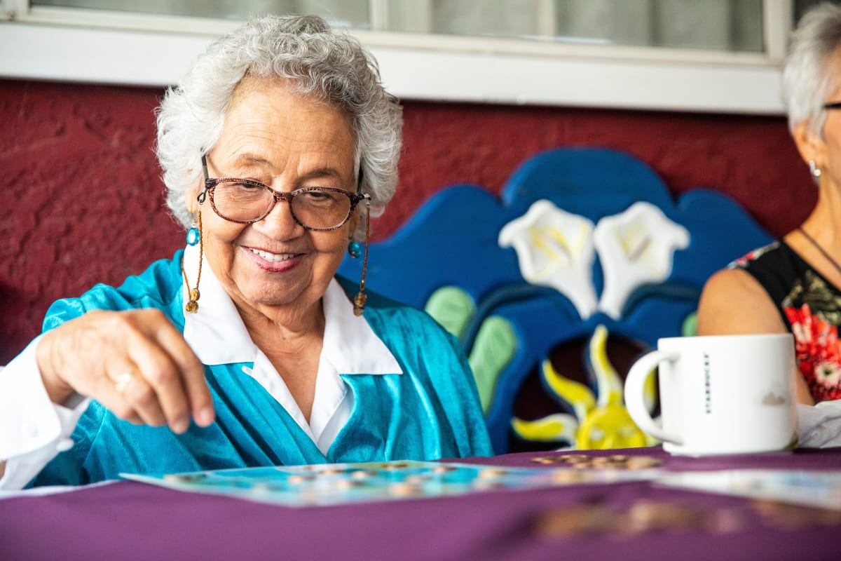 A Memory Care resident enjoying a board game at a Meridian Senior Living community