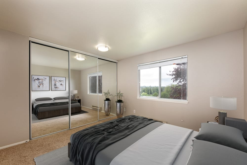 A bedroom with mirrored closet doors at Latitude Apartments in Everett, Washington