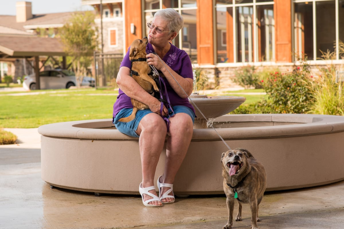 Resident with her dogs at Landing at Watercrest Shadow Creek Ranch in Pearland, Texas