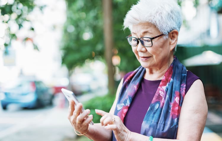 Senior resident on her phone at her new home at The Commons at Woodland Hills in Woodland Hills, California