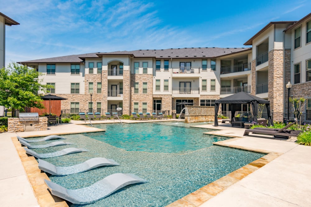 Sparkling pool with loungers in the water at Olympus at Waterside Estates in Richmond, Texas