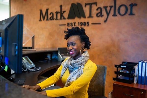 Happy receptionist working the front desk at Mark-Taylor