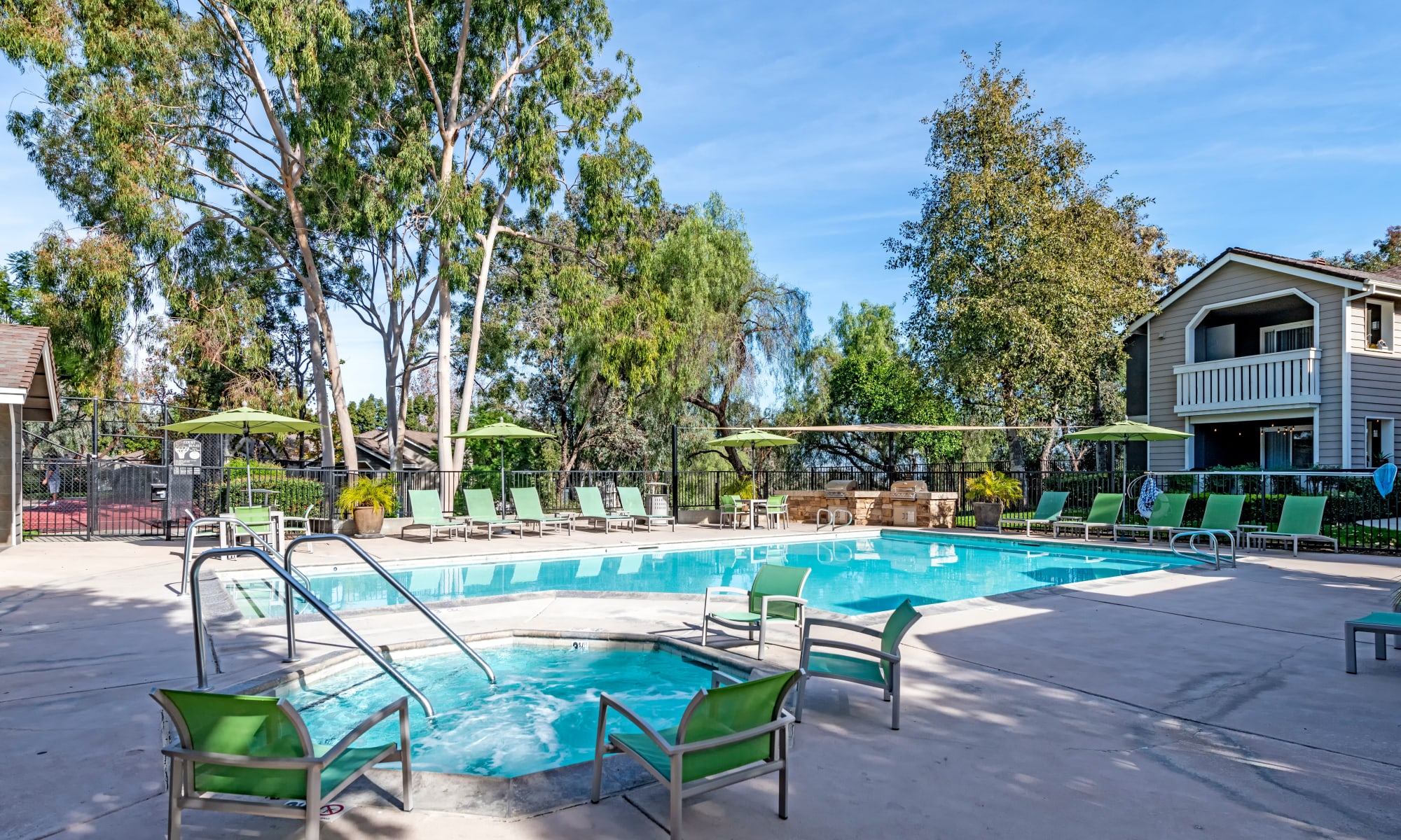 Beautiful pool/spa area with lounge chairs at sunset at Village Oaks in Chino Hills, CA