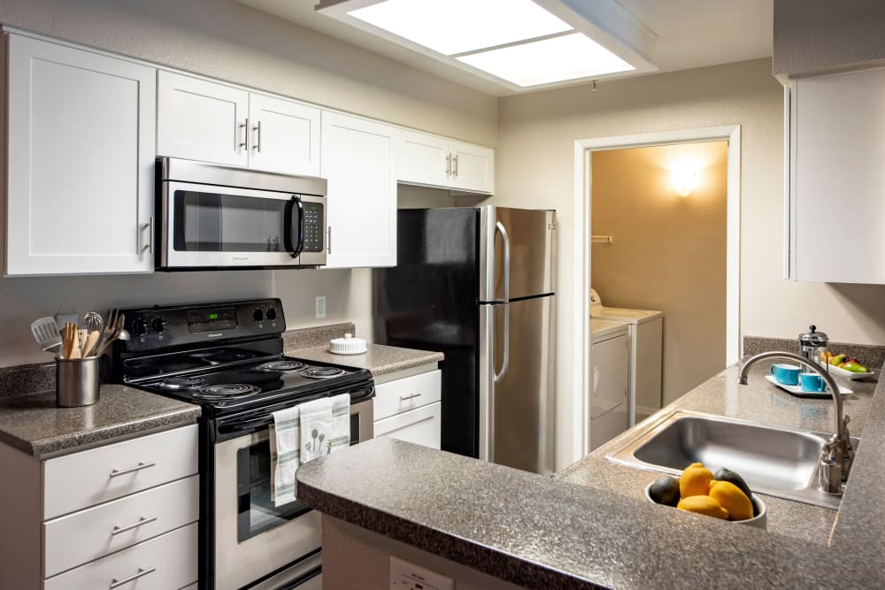 Recently renovated kitchen with stainless steel appliances at Sierra Del Oro Apartments in Corona, California