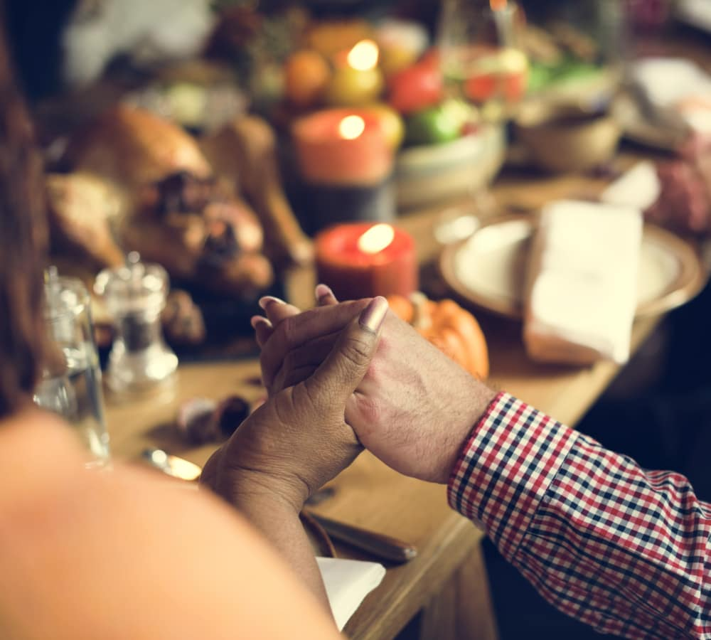Residents Holding hands before a meal at The Creekside in Woodinville, Washington