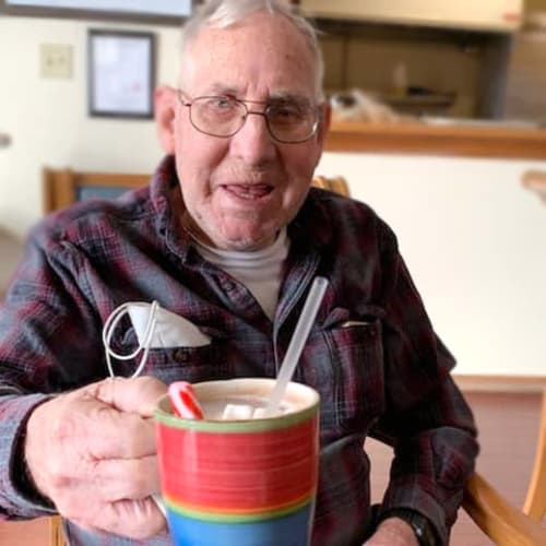 A resident holding a mug of hot chocolate at Alderbrook Village in Arkansas City, Kansas